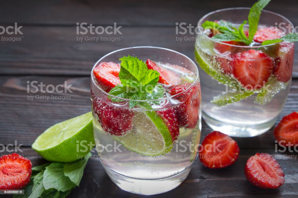 Cold summer drinks in glasses with strawberry , lime and mint stock photo