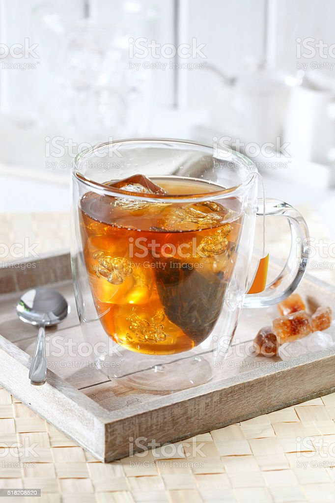 Cold tea with ice cubes on a tray stock photo