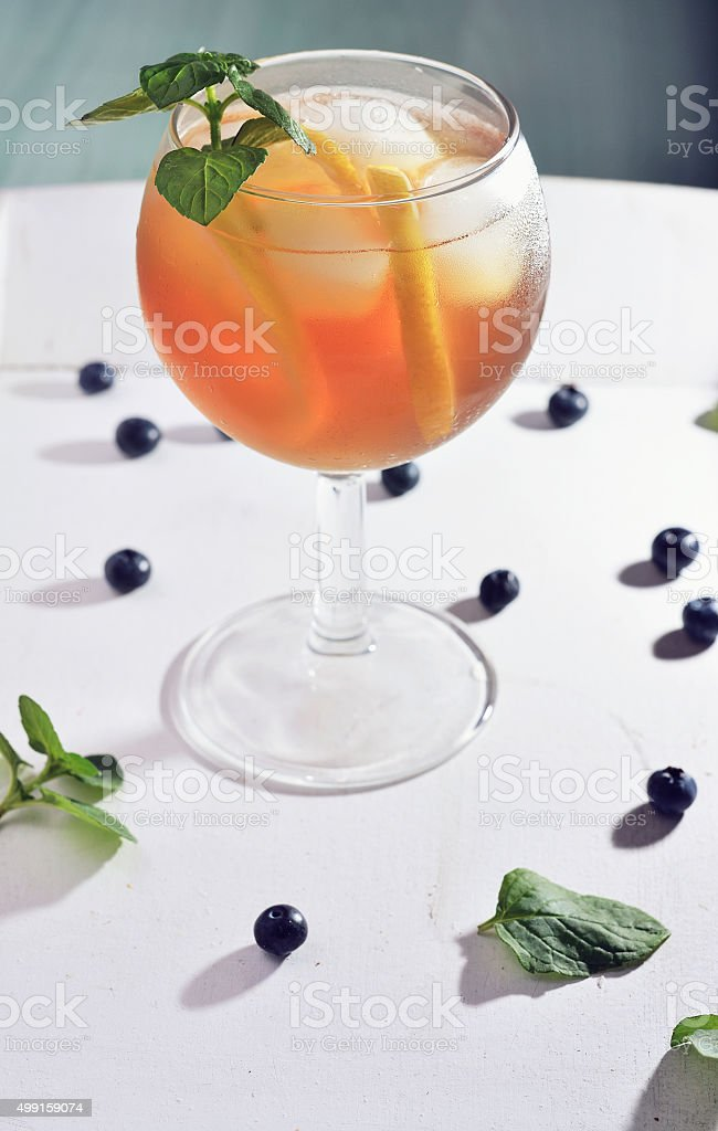 Cold tea with lime on a wooden table whit blueberries stock photo