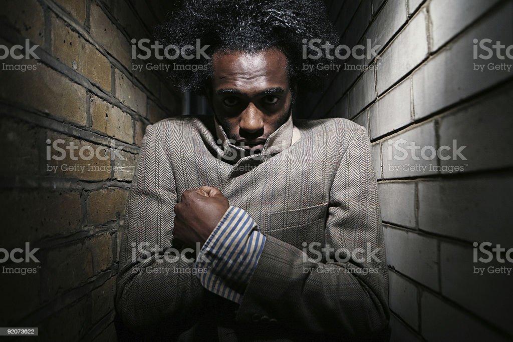 Cold Young Man Between Cozy Brick Walls royalty-free stock photo