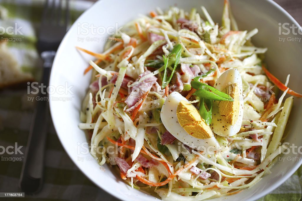 Coleslaw or slaw salad with egg, carrots and ham, close-up royalty-free stock photo