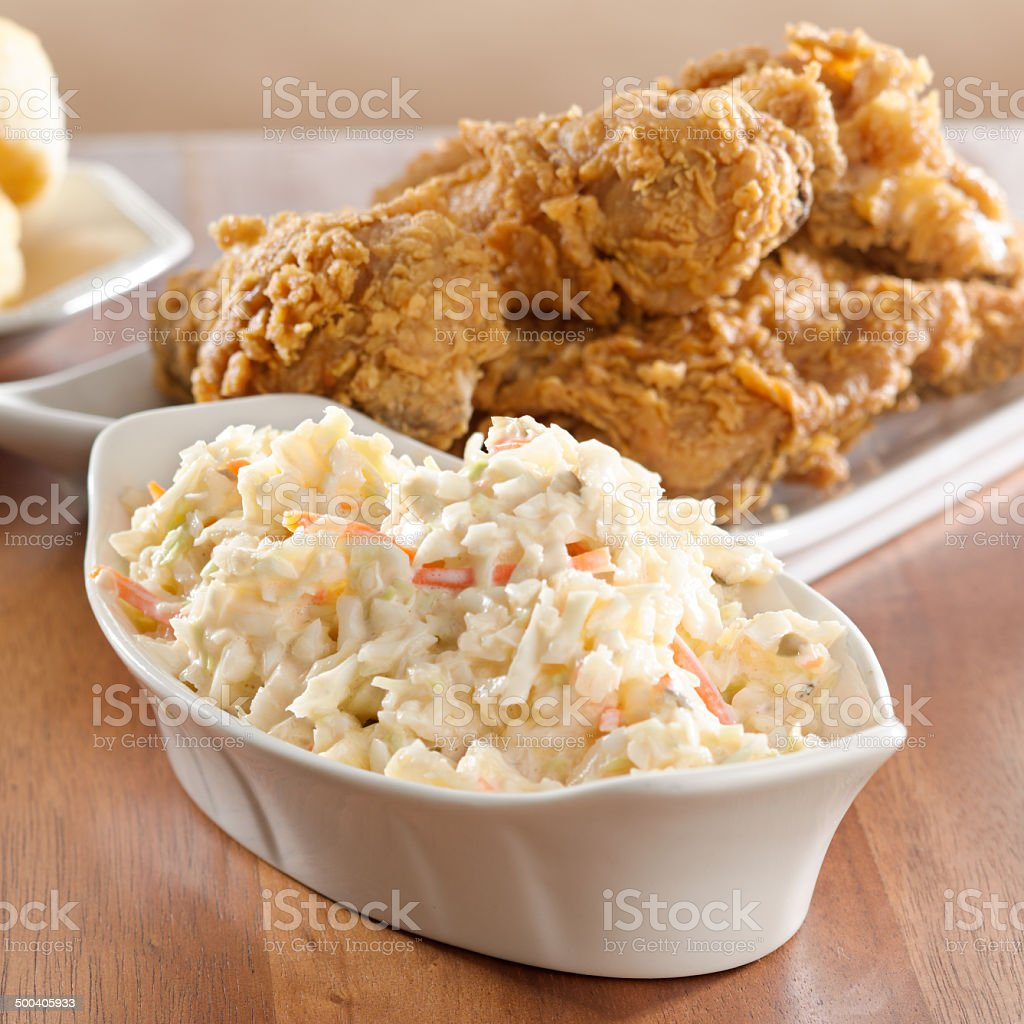 coleslaw with fried chicken in background. stock photo