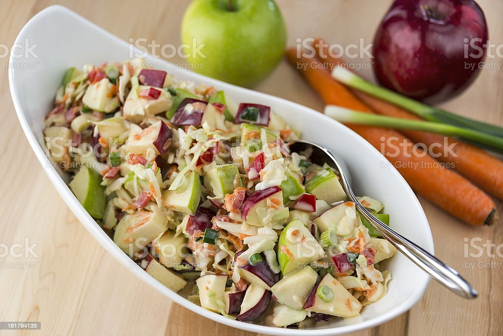 Coleslaw with red and green apples on a wooden table stock photo