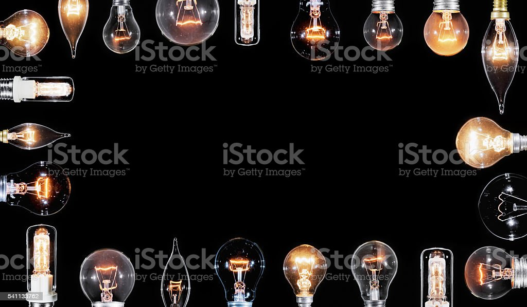 Collage of many Edison lamps glowing over black stock photo