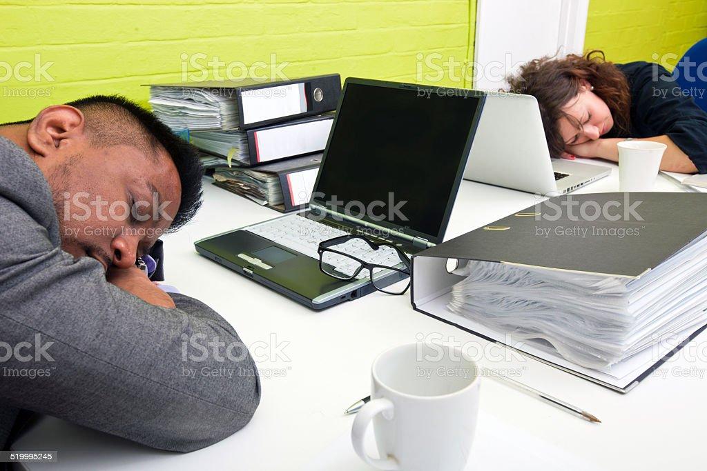 Colleagues asleep at their respective desk stock photo
