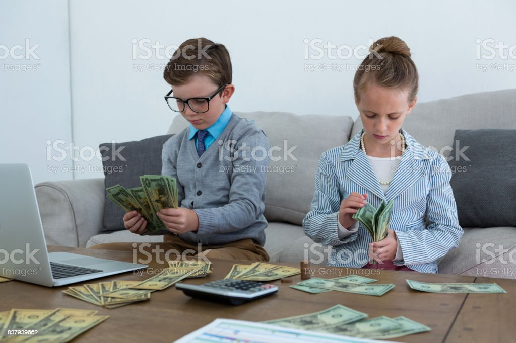 Colleagues counting currency while sitting on sofa stock photo