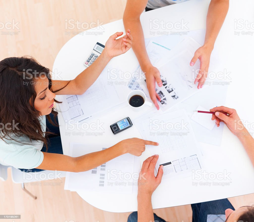 Colleagues discussing documents on table stock photo