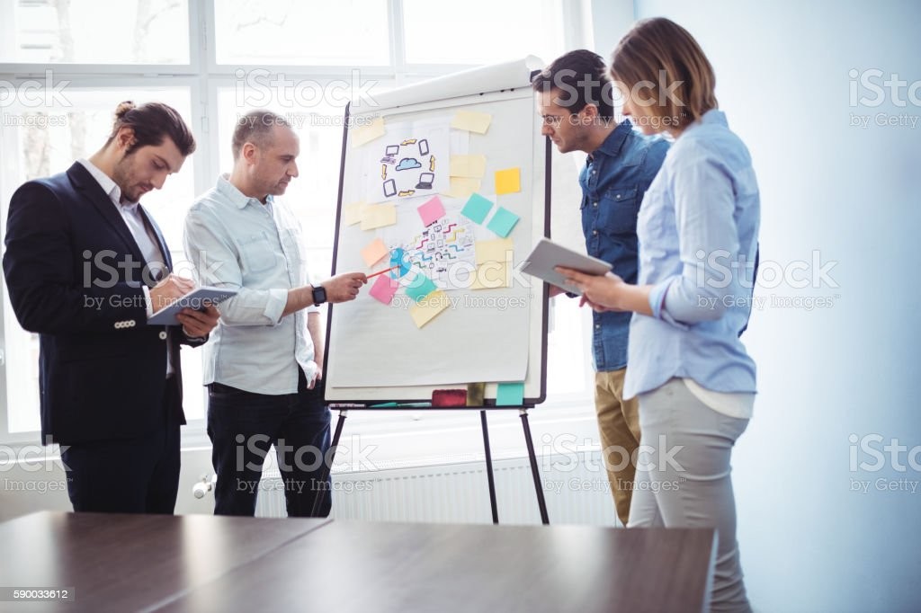 Colleagues discussing in meeting room using white board stock photo