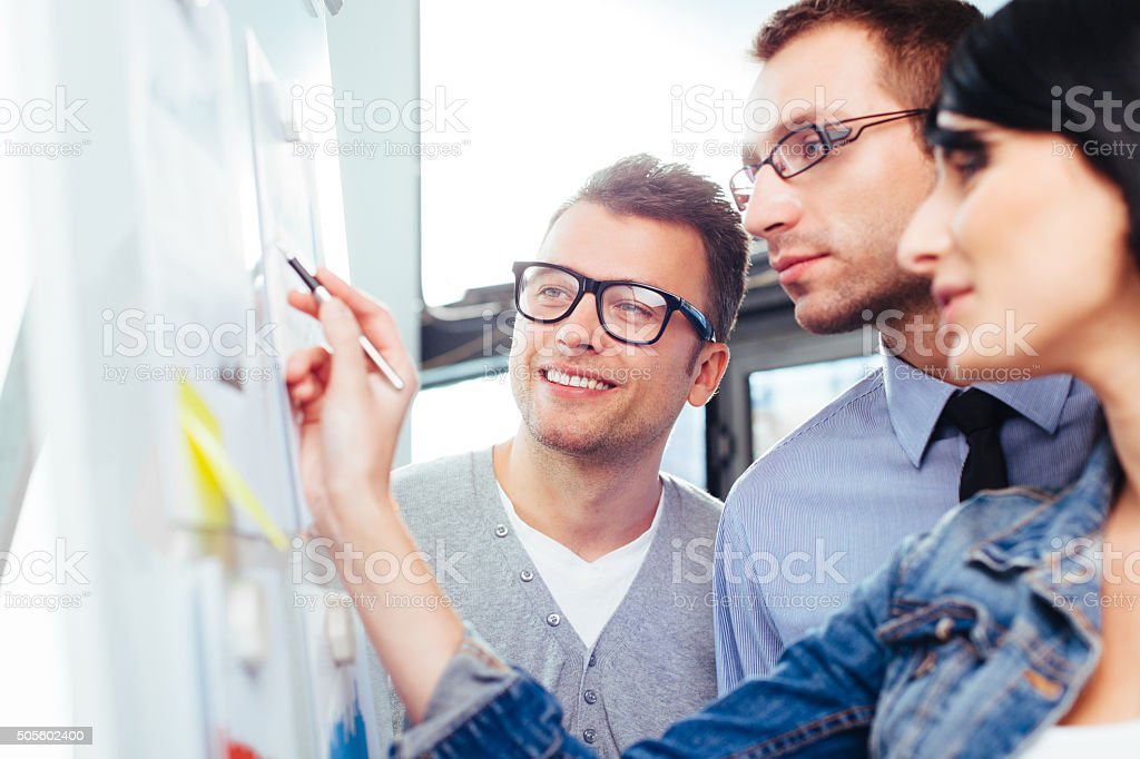 Colleagues discussing their results in front of a board stock photo