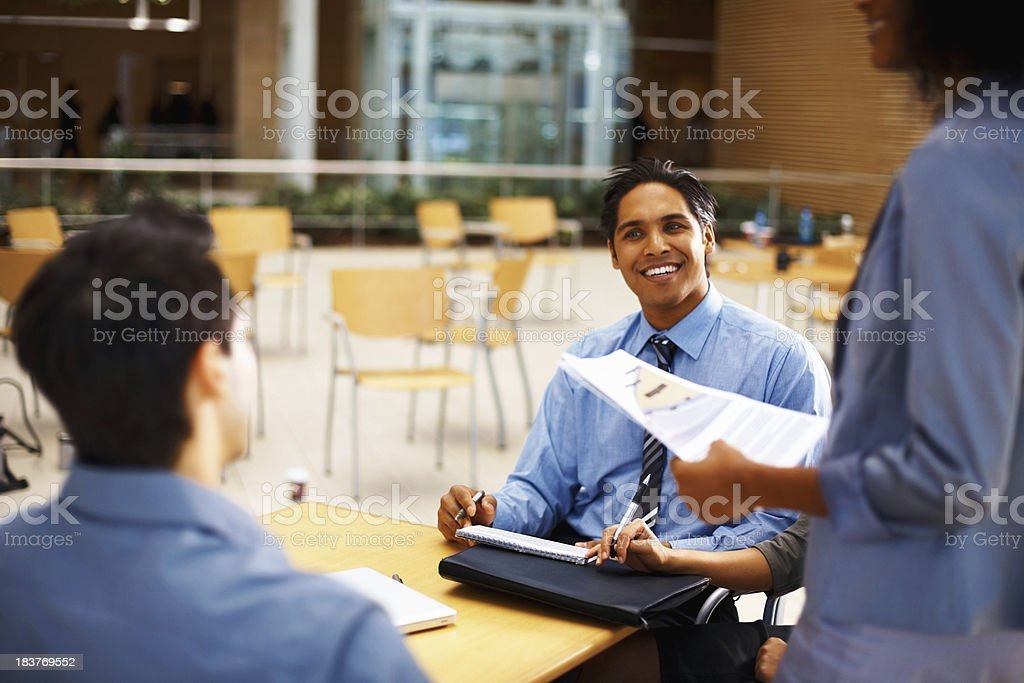 Colleagues discussing work in cafeteria royalty-free stock photo