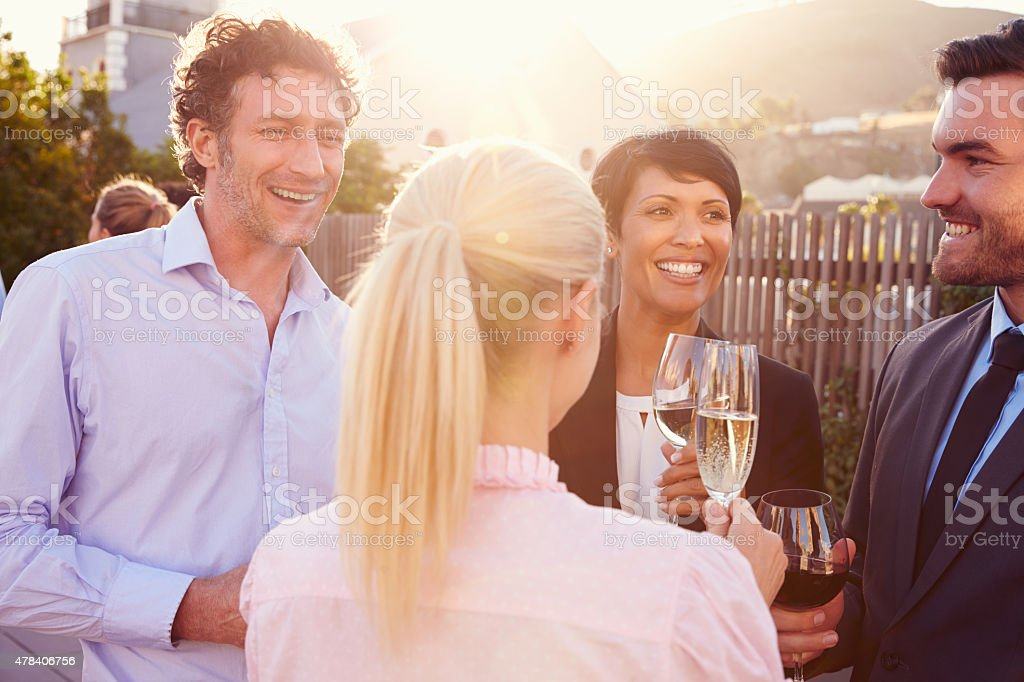 Colleagues drinking after work at a rooftop bar stock photo