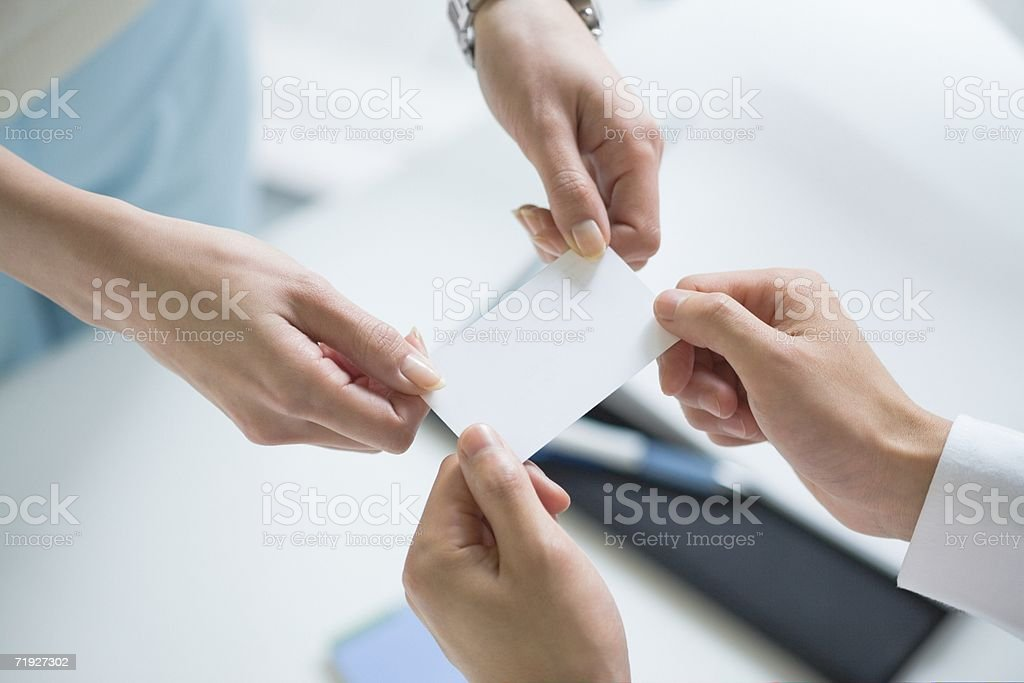 Colleagues exchanging a business card stock photo