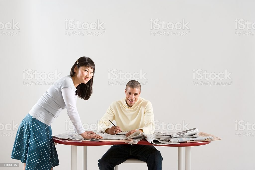 Colleagues going though newspapers royalty-free stock photo