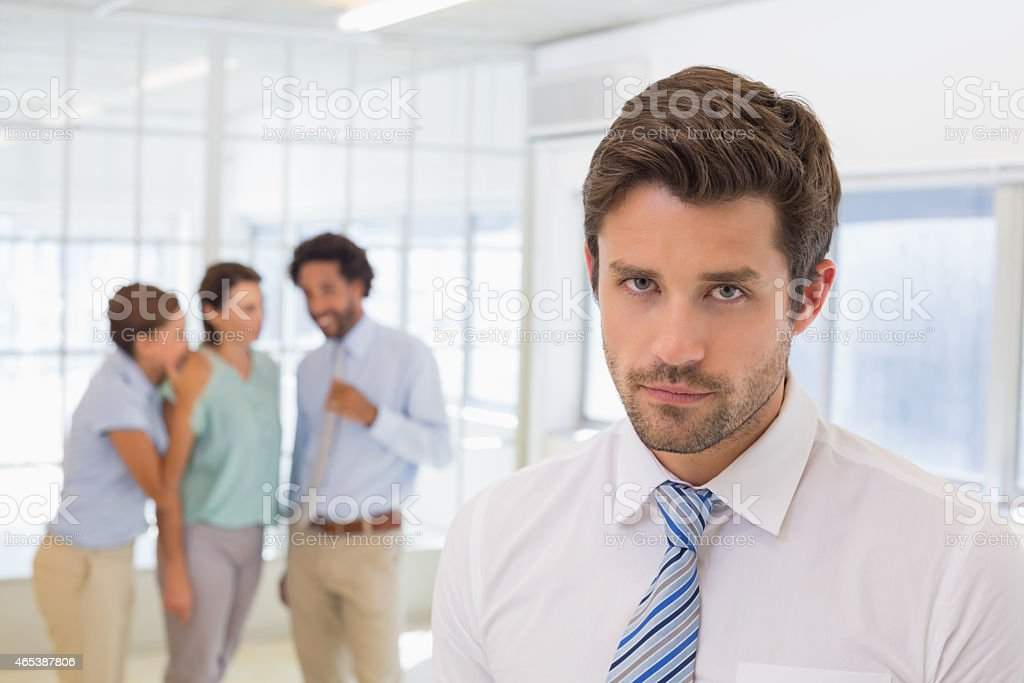 Colleagues gossiping with sad businessman in foreground stock photo