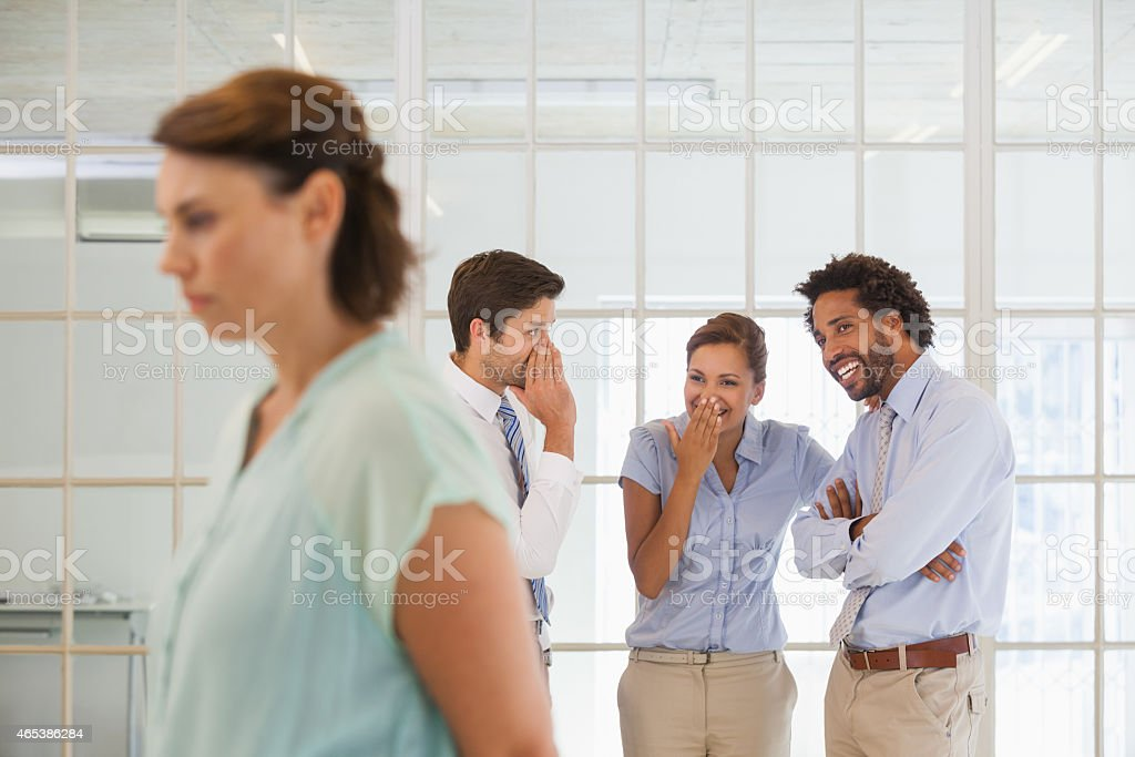 Colleagues gossiping with sad businesswoman in foreground stock photo