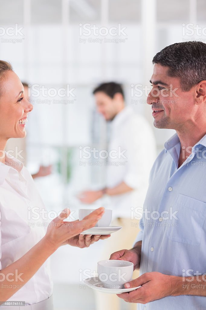 Colleagues in discussion with tea cups during break at office royalty-free stock photo