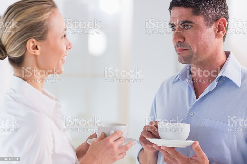 Colleagues in discussion with tea cups during break royalty-free stock photo