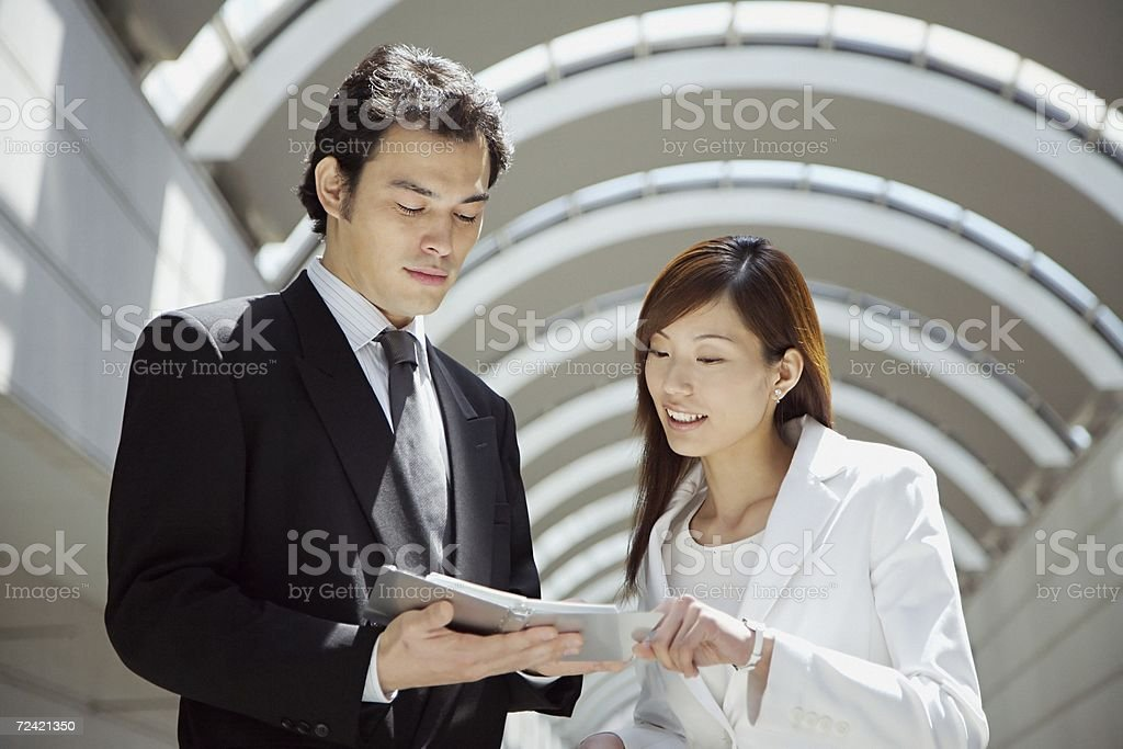 Colleagues looking at organizer stock photo