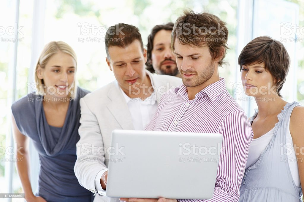 Colleagues reviewing proposal on laptop royalty-free stock photo