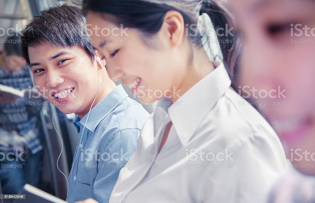 Colleagues riding public transportation together stock photo