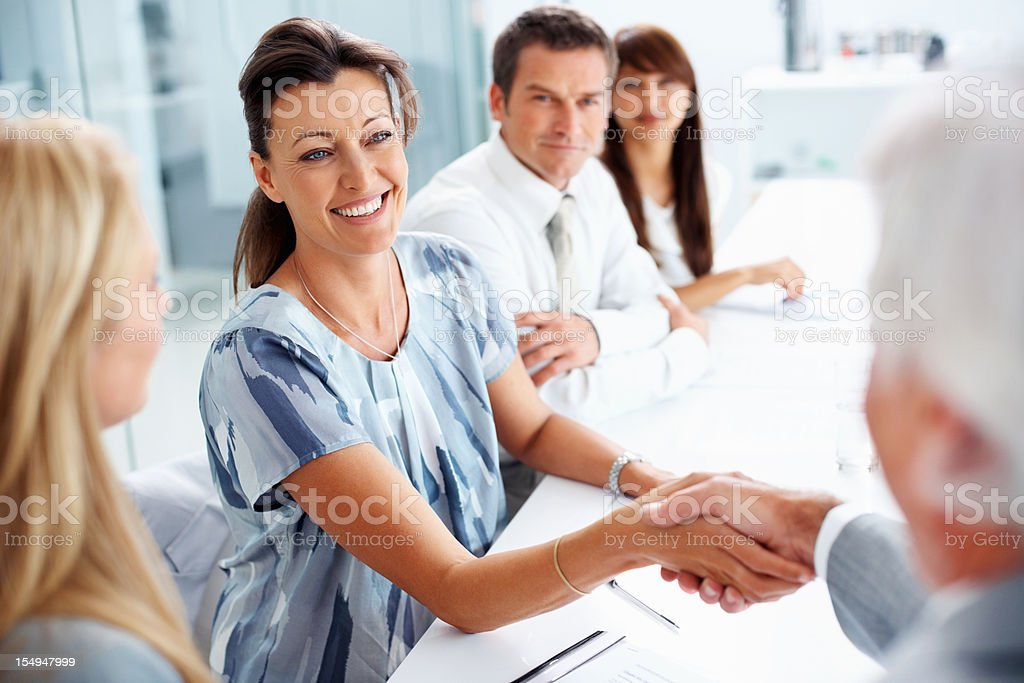 Colleagues shaking hands in meeting royalty-free stock photo
