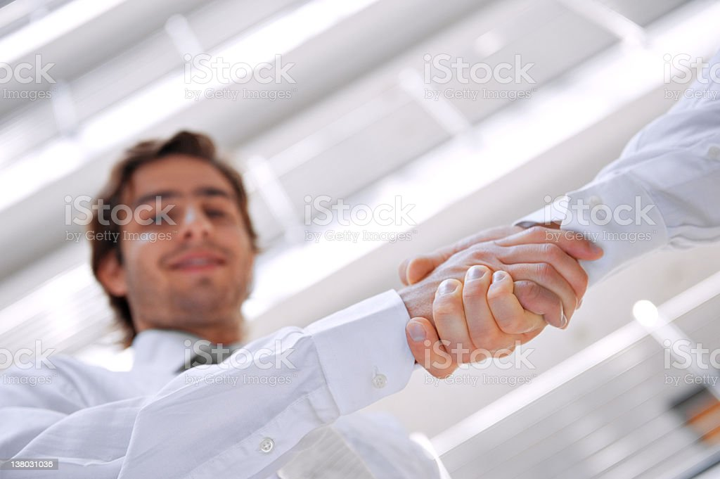 Colleagues shaking hands in office royalty-free stock photo