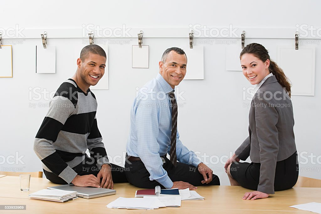 Colleagues sitting on table stock photo