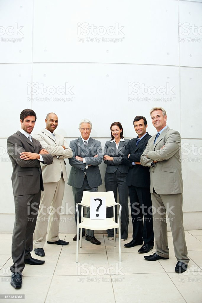 Colleagues standing around a chair with question mark sign royalty-free stock photo