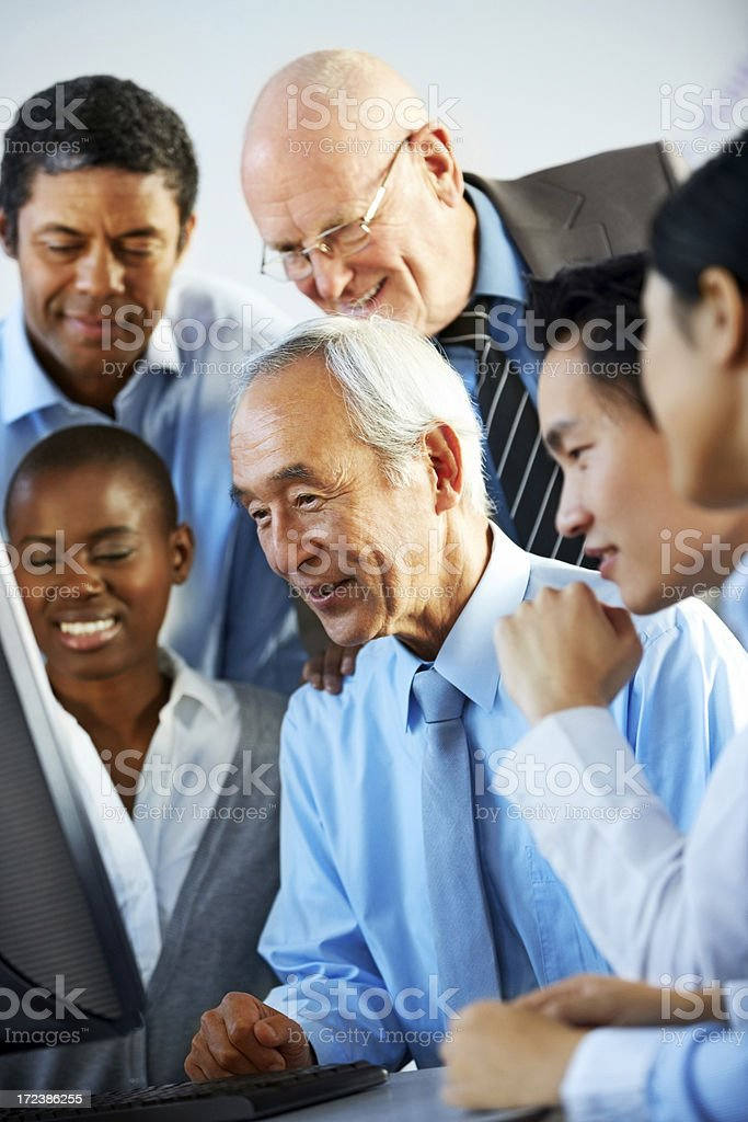 Colleagues surrounding executive as he works on computer royalty-free stock photo