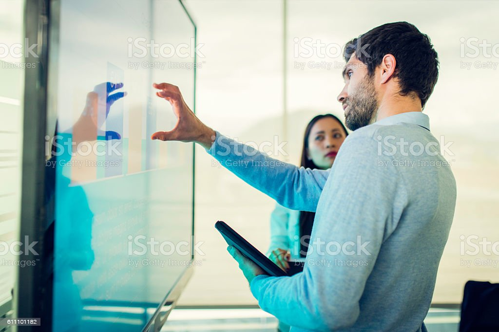 Colleagues talking in front of a screen with a graph stock photo