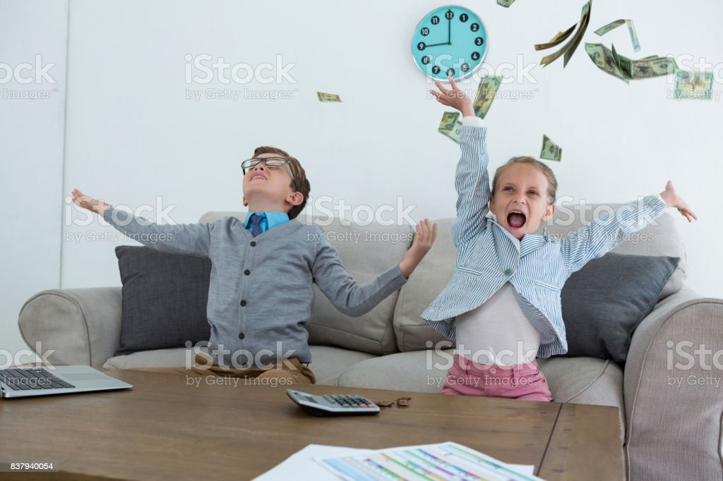 Colleagues throwing currency while sitting on sofa stock photo
