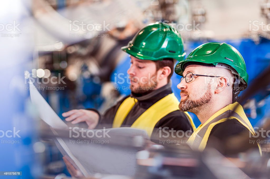 Colleagues with document in brightly lit factory stock photo