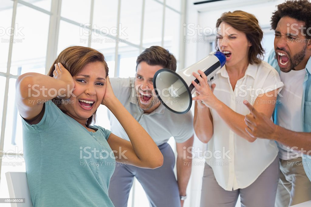 Colleagues yelling through megaphone at businesswoman stock photo