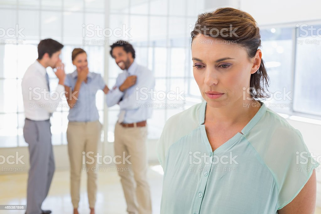 Colleauges gossiping with sad businesswoman in foreground stock photo