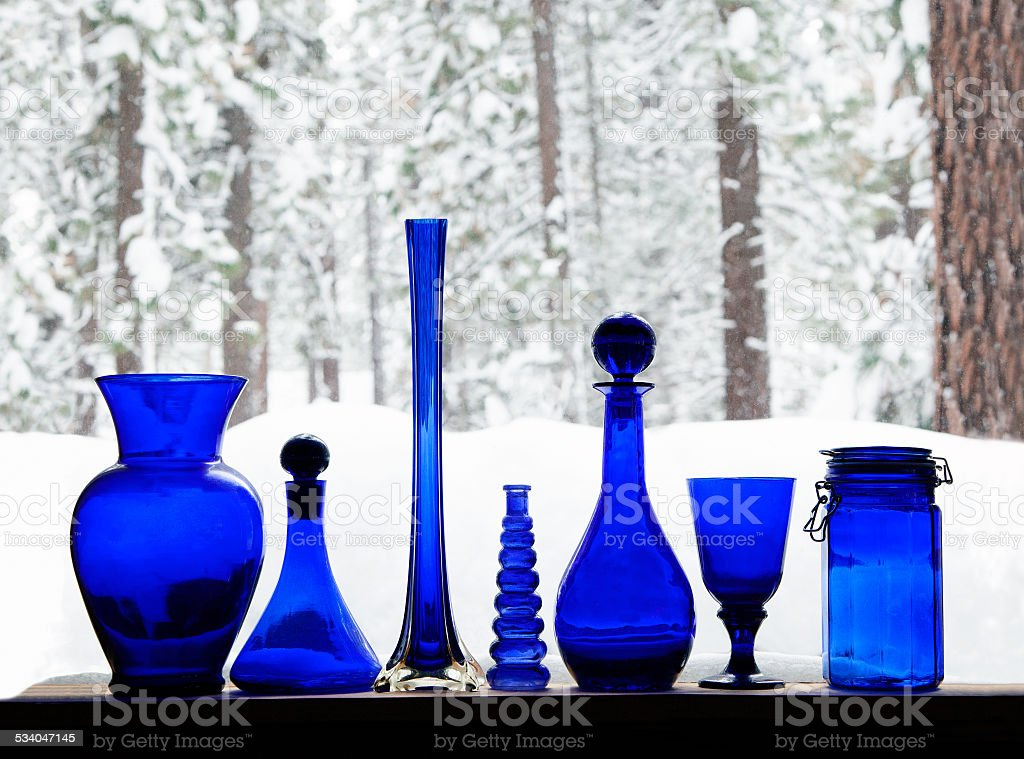 Collectible Blue Glass bottles on a window sill with snow stock photo
