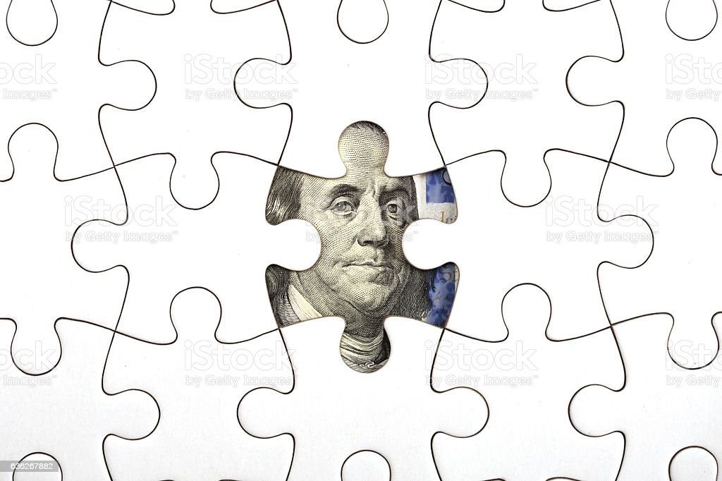 Collecting dollar banknote with jigsaw puzzle stock photo