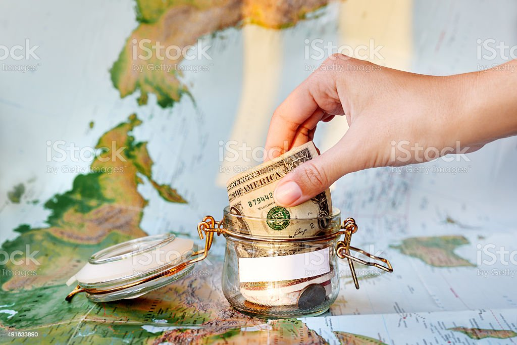 Collecting money for travel. Glass tin as moneybox with cash stock photo