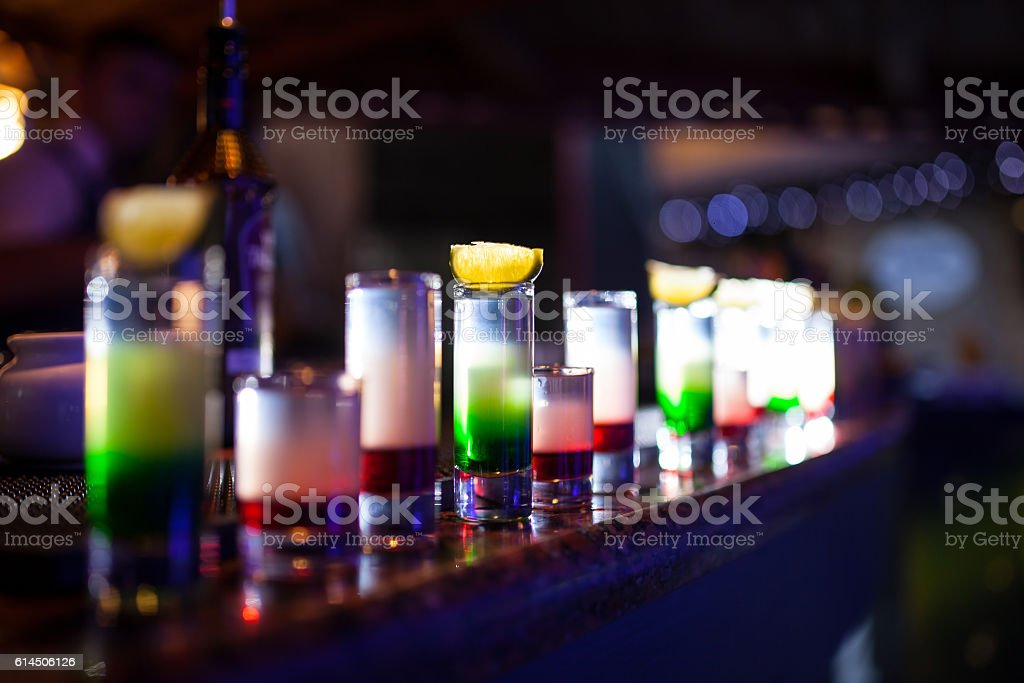 collection of colorful shots with lemon on bar; stock photo