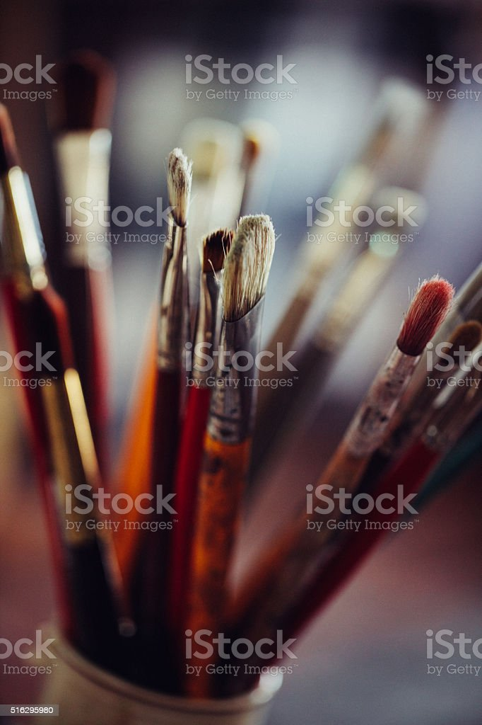 Collection of dirty old artist's paintbrushes in a container stock photo