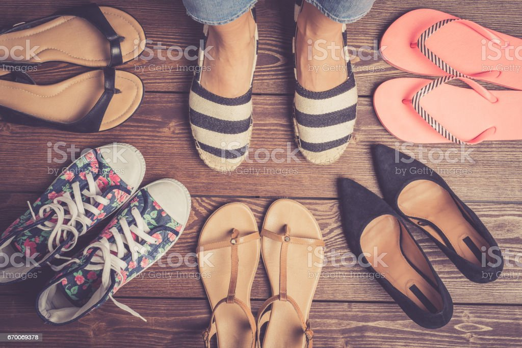 Collection of female shoes on wooden floor. stock photo