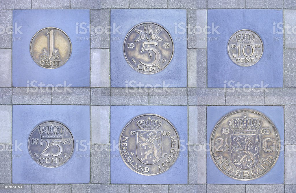 Collection of former Dutch coins in pavement stock photo