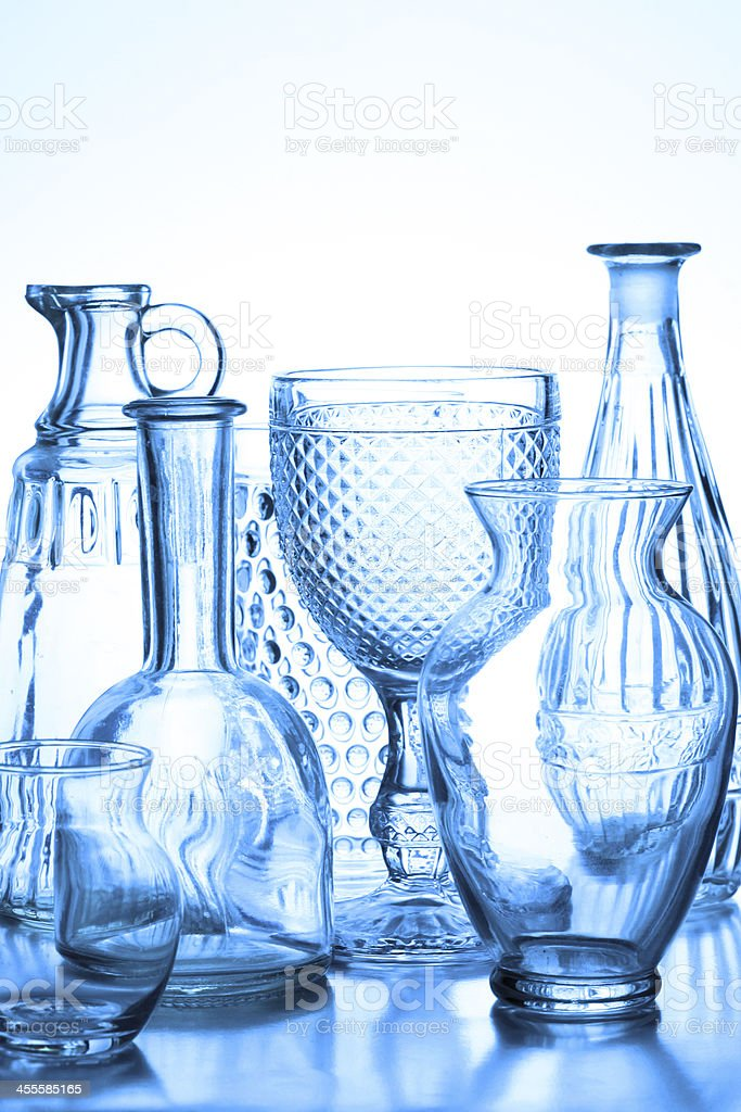 A studio shot of a collection of glass vases, wine glasses and glass...