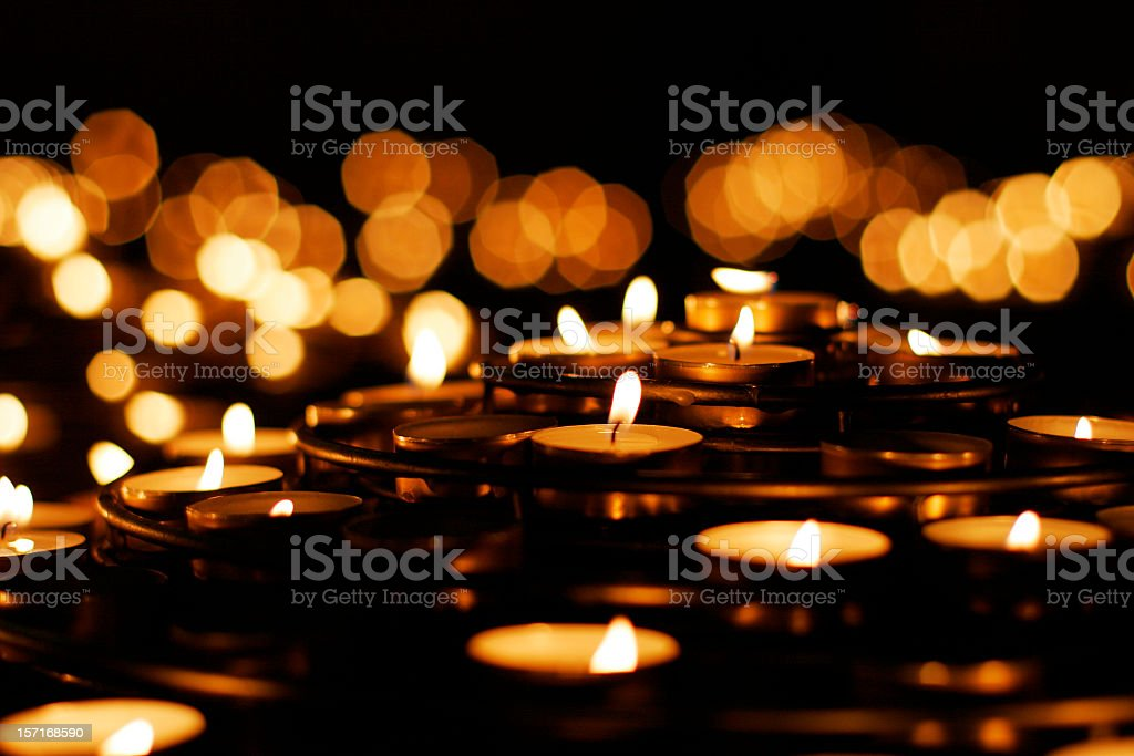 A collection of lit prayer candles against a dark backdrop stock photo