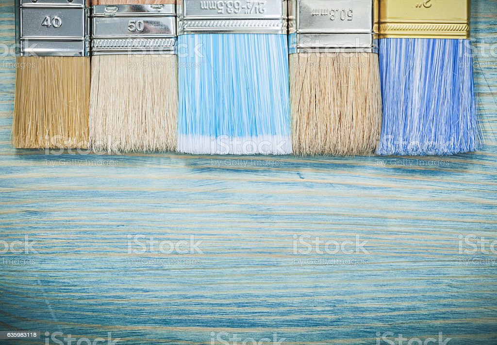 Collection of paint brushes on wood board construction concept stock photo