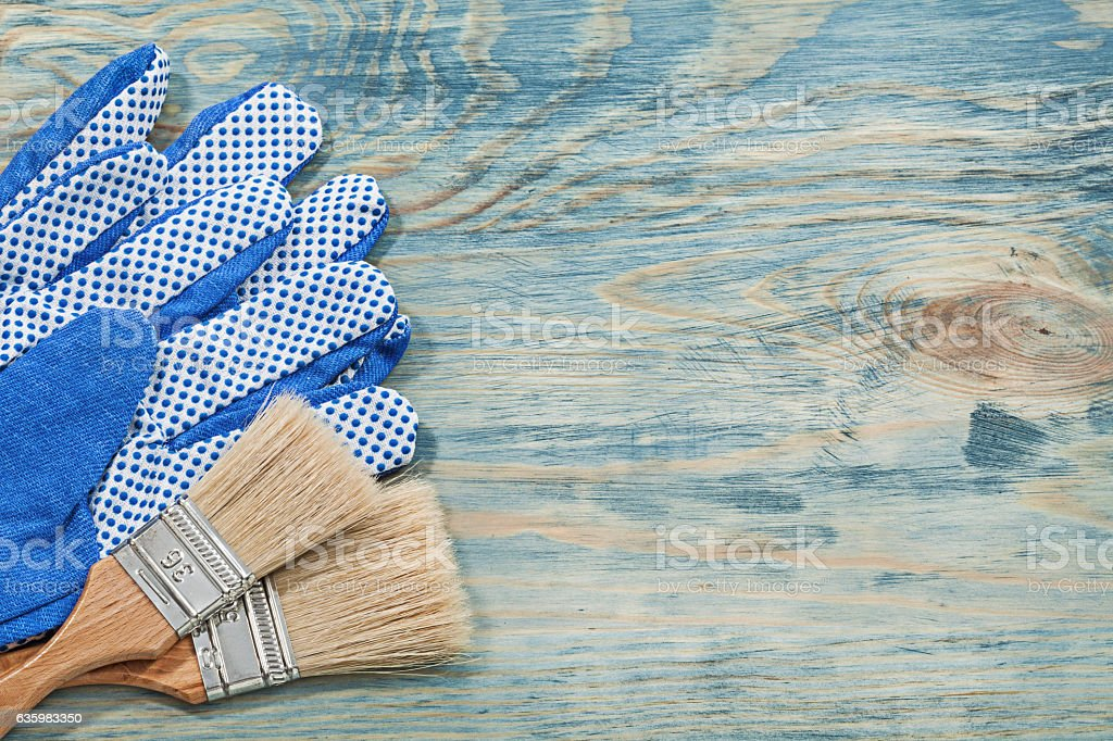 Collection of paintbrushes protective gloves on wooden board con stock photo