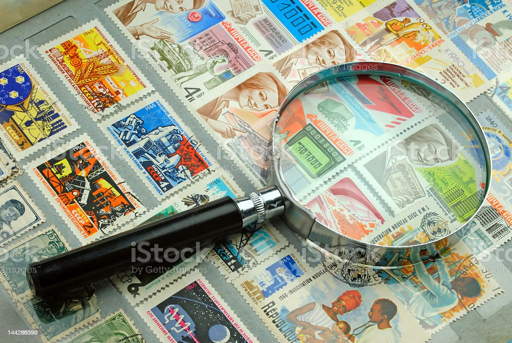 Collection of stamps and magnifier stock photo
