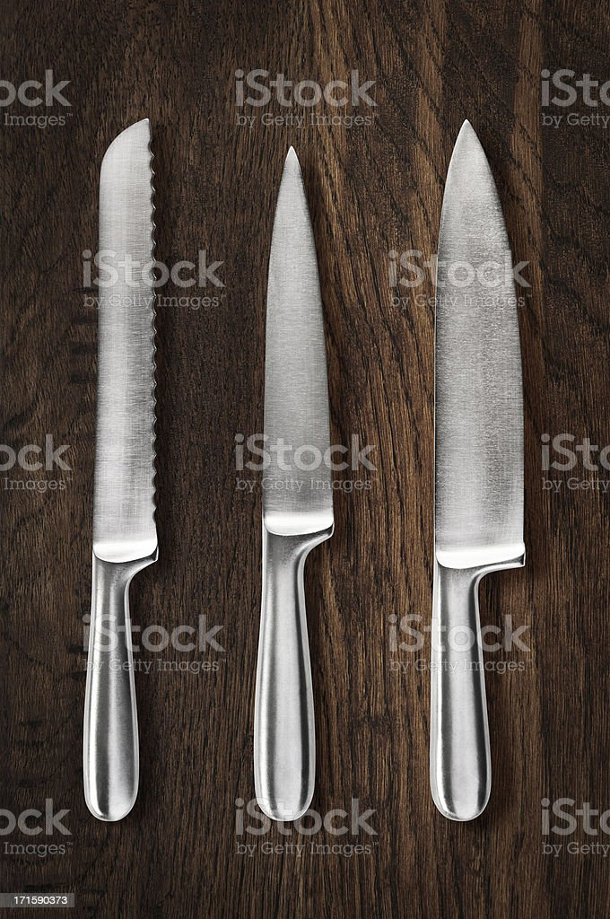 Collection of steel sharp cutting knives on wooden cutting board stock photo