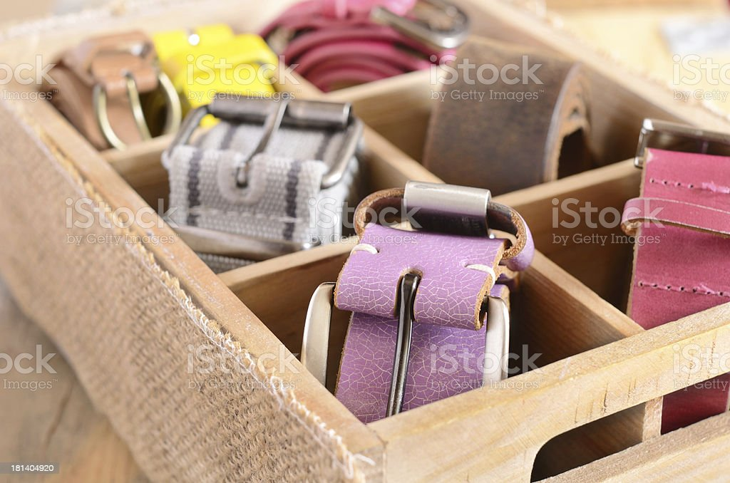 Collection of stylish vintage belts in wooden crate stock photo