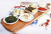 Collection of tapas foods including dates, yogurt, sarma, fresh mozzarella