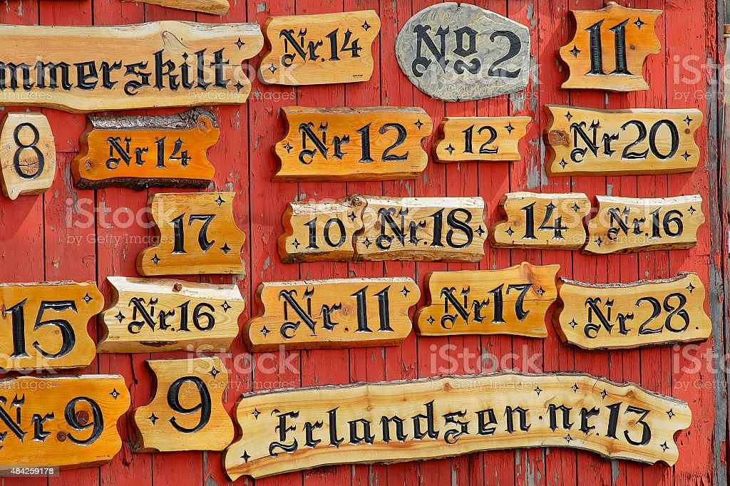 Collection of the wooden house numbers against the red wall. stock photo